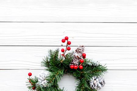 Weihnachtskranz gesponnen von den Fichtenzweigen mit roten Beeren auf Draufsichtkonzept des weißen hölzernen Hintergrundes Draufsicht Standard-Bild - 89907485
