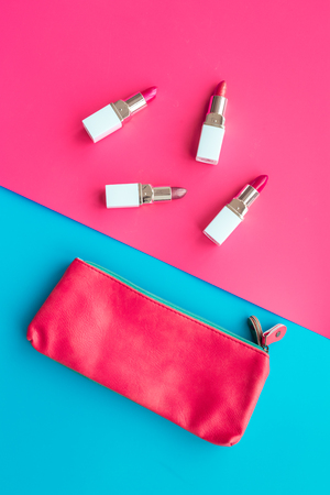 Lipsticks assorted colors near cosmetic bag on blue and pink background top view Stock Photo