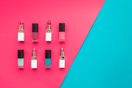 Decorative cosmetics concept. Lipsticks assorted colors and nail polish on red and blue background top view copyspace Stock Photo