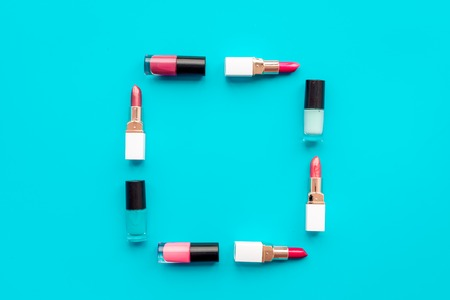 Decorative cosmetics concept. Lipsticks assorted colors and nail polish on blue background top view copyspace