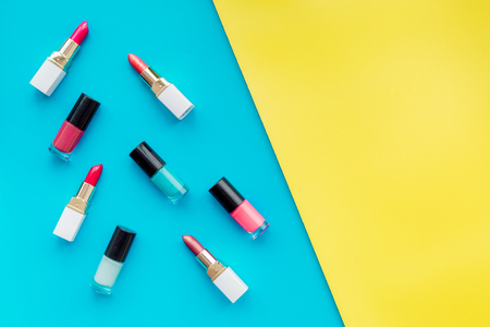 Decorative cosmetics concept. Lipsticks assorted colors and nail polish on yellow and blue background top view copyspace