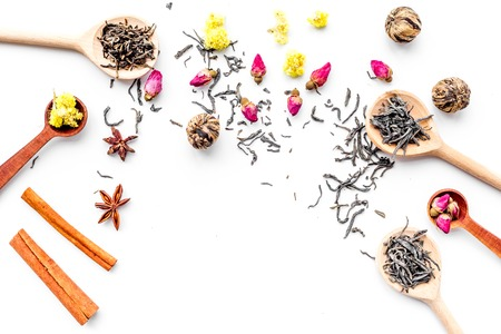 Dried tea leaves near supplements like flowers and spices on white background top view pattern copyspace Stock Photo