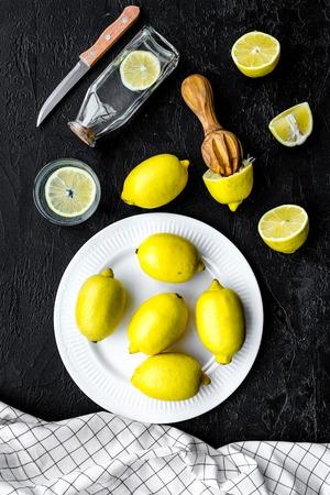 Make lemonade at home. Lemons, juicer, glass and bottle for beverage on black background top view