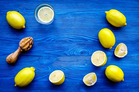 Prepare refreshing beverage lemonade. Lemons, juicer on blue wooden background top view copyspace