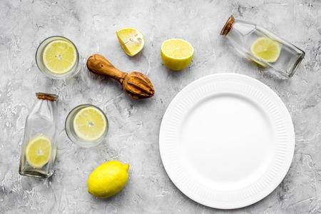 Fresh homemade lemonade. Lemons, juicer, glass for beverage on grey stone background top view mockup