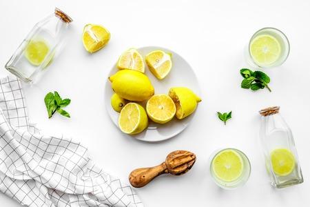 Fresh homemade lemonade. Lemons, juicer, glass for beverage on white background top view