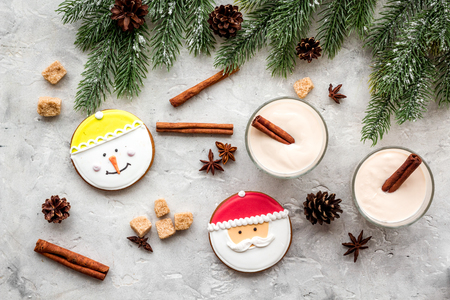 Homemade classic eggnog with cinamon and badian near spruce branch, pinecones, gingerbread on grey stone background top view Stock Photo