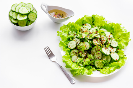 Salad with fresh cucumbers and lettuce near gravy boat. White background copyspace