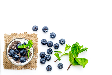 Eat chia seeds for breakfast with yogurt, blueberry and mint. White background top view.