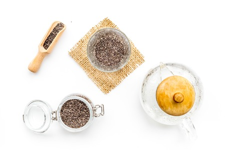 Brew chia seeds. Jar with seeds, scoop, bowl, tea pot with hot water. White background top view.