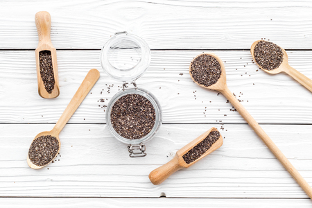 Superfood chia seeds in a wooden spoon and scoop on white wooden background top view. Stock Photo