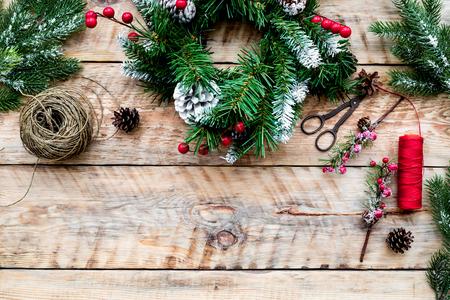 크리스마스 화환을 만드십시오. 가문비 나무 분기, 원뿔, 스레드, 꼬기, sciccors 빛 나무 배경 상위 뷰에.