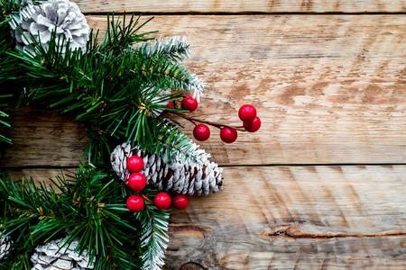 Weihnachtskranz gesponnen von den Fichtenzweigen mit roten Beeren auf heller hölzerner Draufsichtnahaufnahme des Hintergrundes. Standard-Bild - 89908747