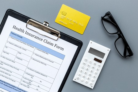 Buy health insurance. Document, bank card and calculator on dark grey background top view.