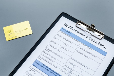 Take out health insurance. Document, bank card on dark grey background.