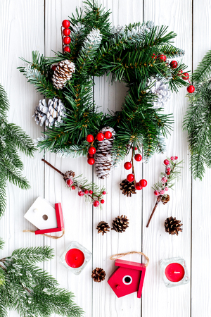 Decorate house for Christmas. Wreath and toys on white wooden background top view.
