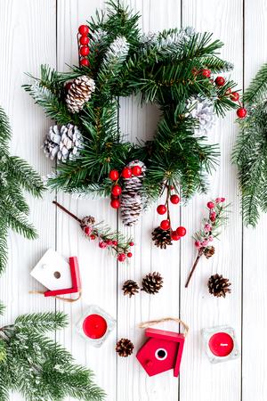 Dekoriere Haus für Weihnachten. Kranz und Spielwaren auf Draufsicht des weißen hölzernen Hintergrundes. Standard-Bild - 89912848