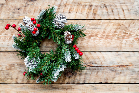 Christmas wreath woven of spruce branches with red berries on light wooden background top view.