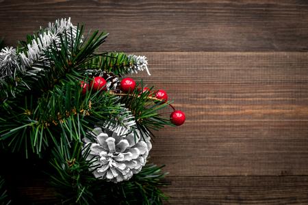 Weihnachtskranz gesponnen von den Fichtenzweigen mit roten Beeren auf Draufsicht des hölzernen Hintergrundes. Standard-Bild - 89912853