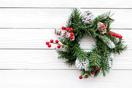 Weihnachtskranz gesponnen von den Fichtenzweigen mit roten Beeren auf Draufsicht des weißen hölzernen Hintergrundes Standard-Bild - 89912678