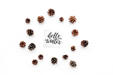 Hello winter hand lettering. Winter pattern with pinecones on white background top view. Imagens - 89912778