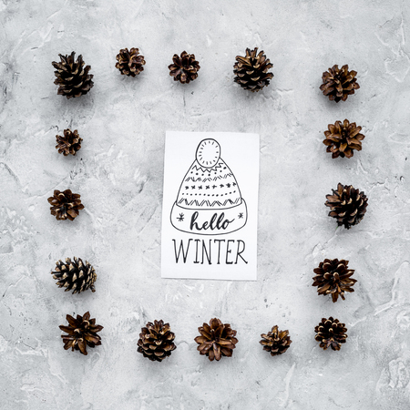 Hello winter hand lettering with hat icon. Winter pattern with pinecones on grey background top view. Imagens - 89912775