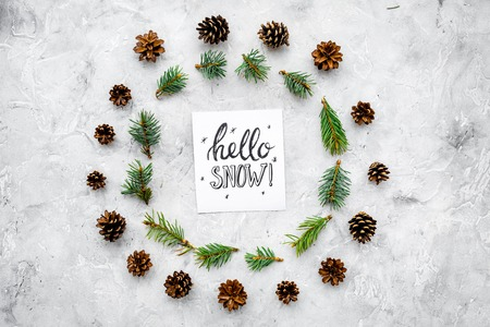 Hello snow hand lettering. Winter pattern with pinecones and spruce branch on grey background top view.