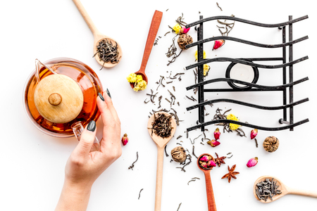 Brew tea with flowers and spices. Hand hold tea pot on white background top view.