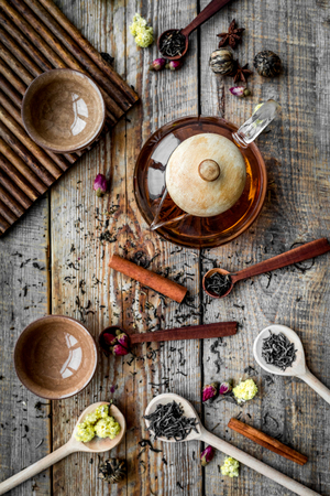 Tea party set. Tea pot, cups, dried tea leaves, fllowers, spices on wooden background top view. Banco de Imagens