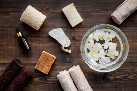 Bath in bowl with tropical flowers for foot spa, pumice stone, soap and oil on dark wooden background top view. Stock Photo