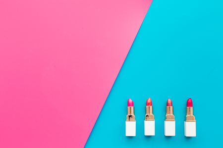 Lipsticks assorted colors on blue and pink background top view. Stock Photo