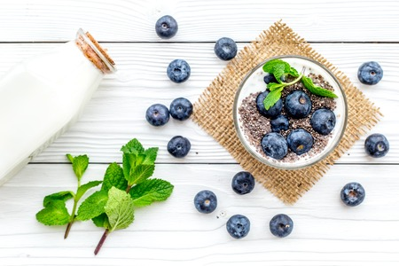Eat chia seeds for breakfast with yogurt, blueberry and mint. White wooden background top view. Stock Photo