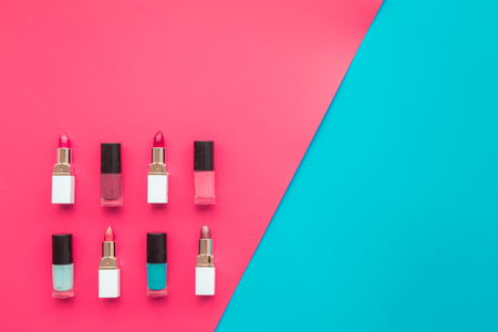 Decorative cosmetics concept. Lipsticks assorted colors and nail polish on red and blue background top view.