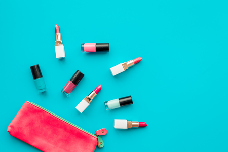 Decorative cosmetics concept. Lipsticks assorted colors and nail polish on blue background top view.