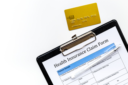 Buy health insurance. Document, pad, pen and bank card on white background top view. Stock Photo
