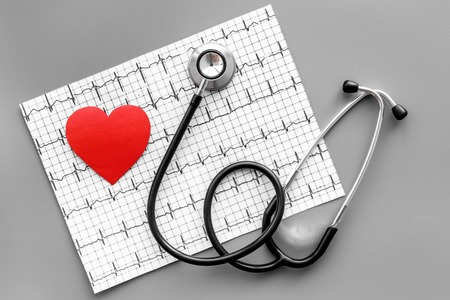 Examine the heart to prevent heart disease. Heart sign, cardiogram, stethoscope on grey background top view