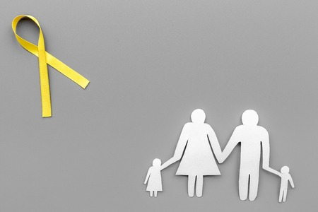 Yellow ribbon for suicide and endometriosis awareness near paper silhouette of family on grey background top view copyspace Stock Photo
