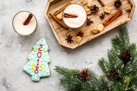 Homemade classic eggnog with cinamon and badian near spruce branch, pinecones, gingerbread on grey stone background top view. Stock Photo