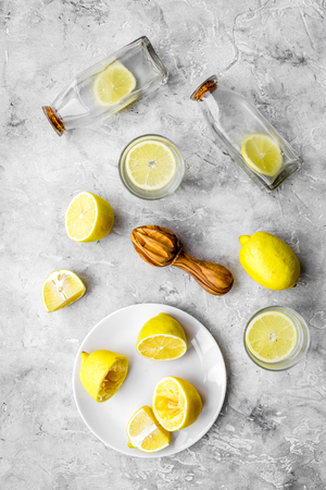 Fresh homemade lemonade. Lemons, juicer, glass for beverage on grey stone background top view
