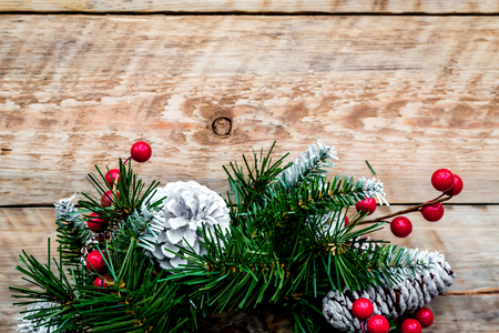 Christmas wreath woven of spruce branches with red berries on light wooden background top view closeup copyspace