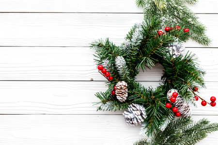 Christmas wreath woven of spruce branches with red berries on white wooden background top view
