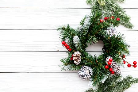 Weihnachtskranz gesponnen von den Fichtenzweigen mit roten Beeren auf Draufsicht des weißen hölzernen Hintergrundes Standard-Bild - 90054141