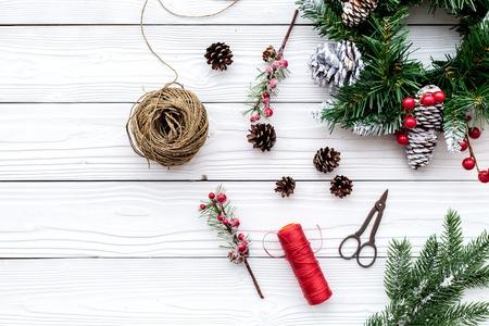 Weihnachtskranz machen. Fichtenzweige, Kegel, Threads, Schnur, sciccors auf weißem hölzernem Draufsicht copyspace des Hintergrundes Standard-Bild - 90064165