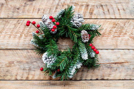 Christmas wreath woven of spruce branches with red berries on light wooden background top view Stock Photo
