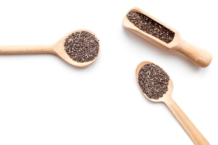 Superfood chia seeds in a wooden spoon and scoop on white background top view copyspace