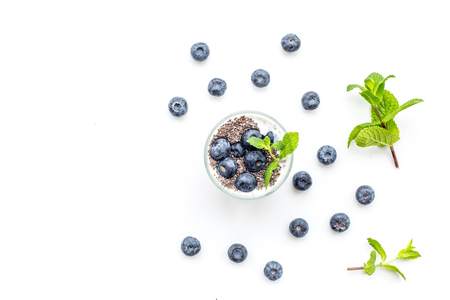 Light dessert with chia seeds, yogurt, blueberry and mint. White background top view copyspace