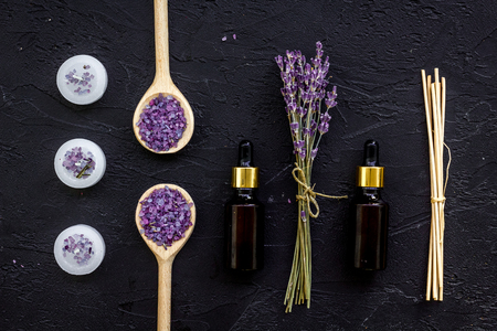 Aromatherapy for relax concept. Lavender branch, spa salt, oil and candles on black background top view