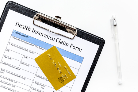 Buy health insurance. Document, pad, pen and bank card on white background top view