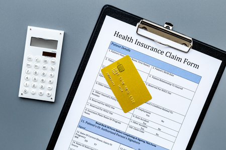 Buy health insurance. Document, bank card and calculator on dark grey background top view Stock Photo