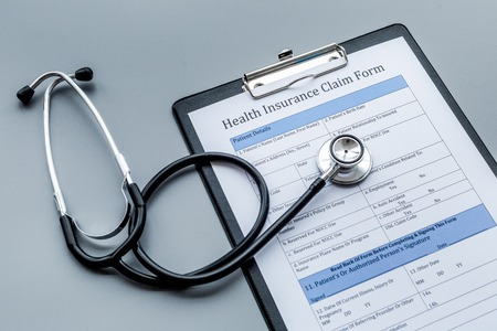 Health insurance for reception at the doctor. Document and stethoscope on dark grey background Stock fotó